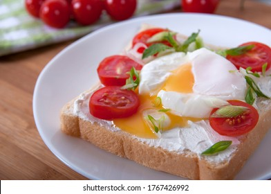 A delicious breakfast with poached egg, bread, cherry tomatoes, cheese and herbs. Poached egg for breakfast. Sandwich with cheese, red cherry tomatoes, herbs and poached egg.