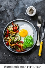 Delicious breakfast or snack - grilled vegetables and fried egg on a dark background, top view