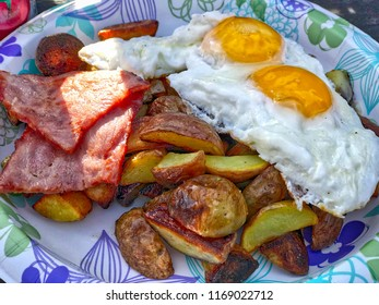 Delicious breakfast with sunny-side fried eggs, fried potato and ham. Close up