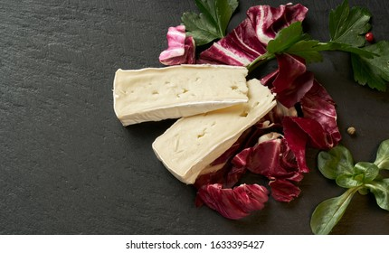 Delicious brie cheese with lavender on black background. Brie type of cheese. Camembert. Fresh Brie cheese and a slice on stone board. Italian, French cheese