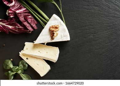 Delicious brie cheese on black background. Brie type of cheese. Camembert. Fresh Brie cheese and a slice on stone board. Italian, French cheese.