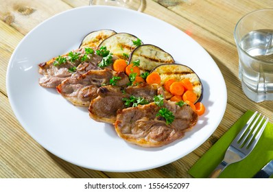 Delicious broiled lamb loin chops served on white plate with grilled eggplant and carrots