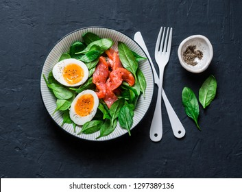 Delicious brunch - spinach, smoked salmon, soft boiled egg on a dark background, top view. Healthy eating diet concept