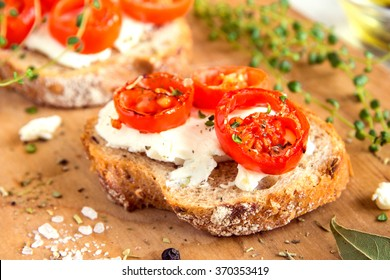 Delicious bruschetta with roasted tomatoes, feta cheese and herbs on wooden board