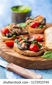 Delicious bruschetta with tomatoes and mushrooms on cutting board on the table
