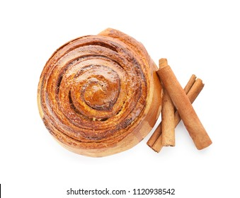 Delicious bun and cinnamon sticks on white background