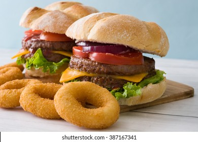 Delicious burger with cheddar cheese, tomato, lettuce and onion. Blue background