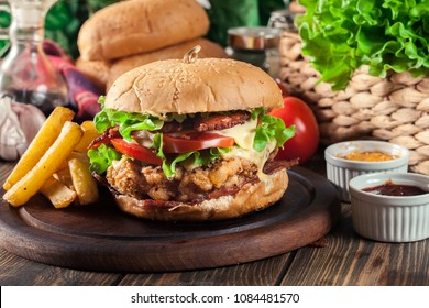 Delicious burger with chicken, bacon, tomato, cheese and lettuce served with french fries
