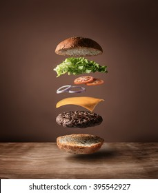 Delicious burger with floating ingredients on the wood table background