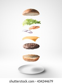 Delicious burger with floating ingredients on white background