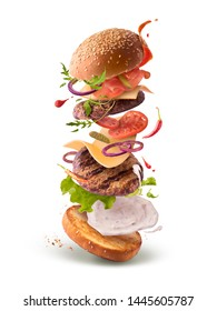 Delicious burger with flying ingredients isolated on white background