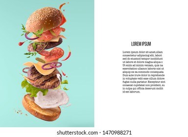 Delicious burger with flying ingredients isolated on turquoise background. Food levitation concept. High resolution image