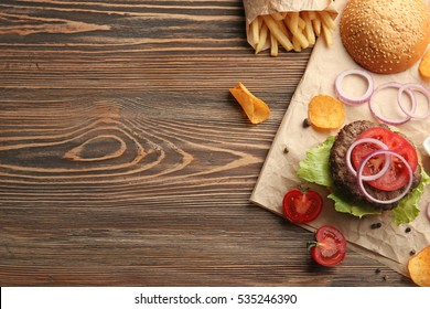 Delicious burger and fresh tomatoes on wooden background