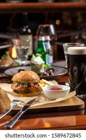 Delicious burger and glass of dark beer on wooden table at restaurant side view