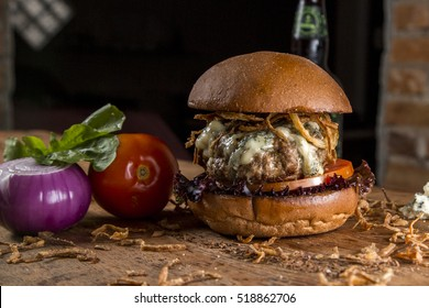 Delicious burger with gorgonzola cheese and crispy onion on top of a rustic wooden table