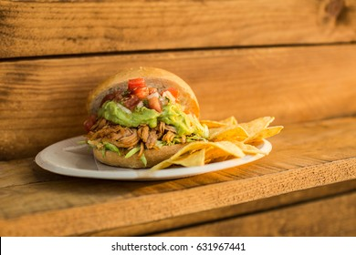 Delicious burger served on plate with nacho chips.