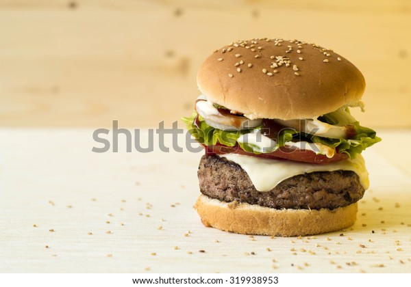 Delicious burgers with beef, tomato, cheese, onion and lettuce with copyspace