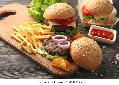 Delicious burgers and snacks on wooden table closeup