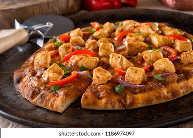 A delicious butter chicken pizza with red pepper, red onion and cilantro.