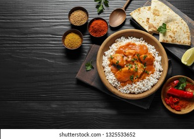 Delicious butter chicken with rice served on wooden table, flat lay. Space for text