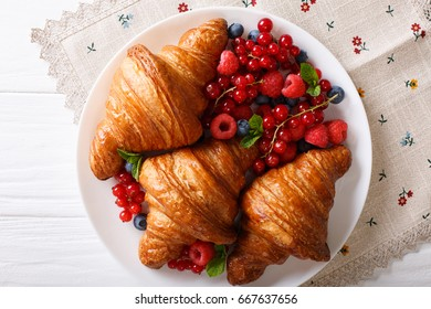 Delicious butter croissant with fresh berries close up on a plate. horizontal view from above