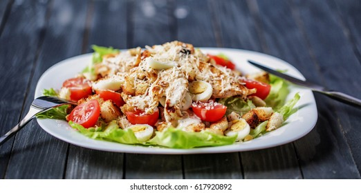 Delicious Caesar salad with cherry tomatoes and Parmesan on a beautiful wooden background