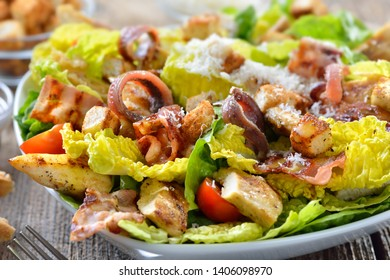 Delicious Caesar Salad with grilled chicken, bacon, croutons, anchovy fillets and parmesan cheese