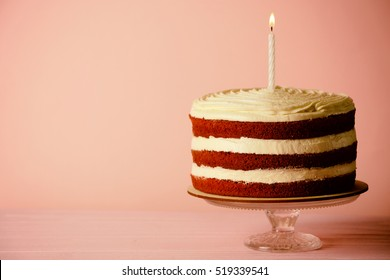 Delicious cake with candle on pink background