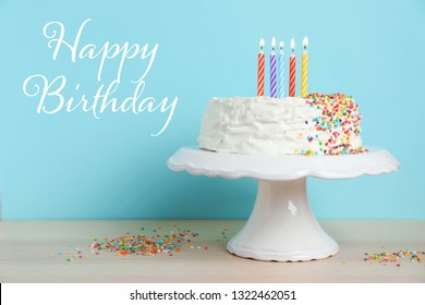 Delicious cake with candles and text Happy Birthday against blue background