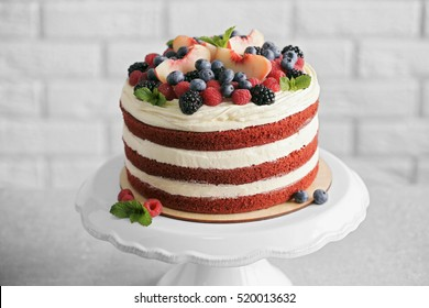 Delicious cake with fruit and berries decoration on gray table