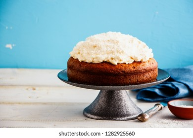 Delicious cake with mascarpone cream and coconut on blue background