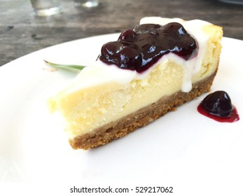 Delicious cake pour with blueberry jam on the white plate.