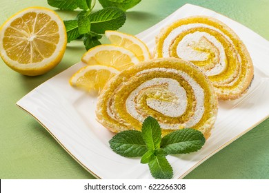 Delicious cake roll with lemon marmalade and marshmallow. Sliced rolls on a plate, lemon and mint. Tasty fruit dessert