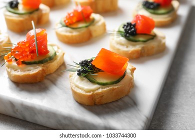 Delicious canapes with black and red caviar on board
