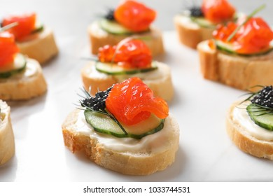 Delicious canapes with black and red caviar on light background