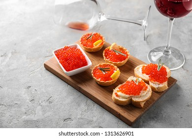 Delicious canapes with red caviar and glass of wine on grey table