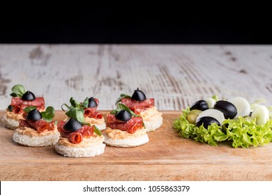 Delicious canapes with salami, olives and spices on a wooden background