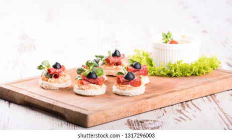 Delicious canapes with salami, olives and spices on a wooden background - Image