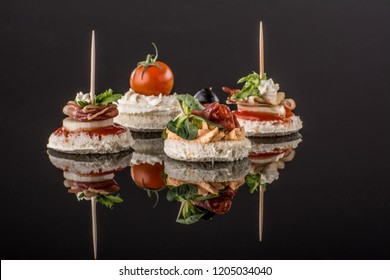 Delicious canapes with salami,cheese,salads,olive and spices at luxury black background with reflection