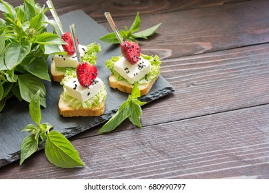 Delicious canapes wiyh feta cheese and strawberrys on background of fresh basil leaves.Banquet service