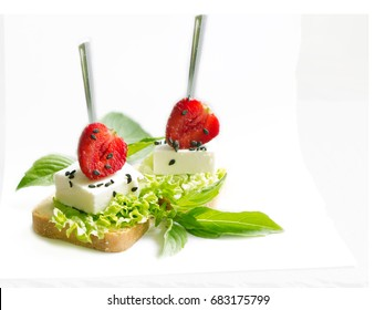 Delicious canapes wiyh feta cheese , strawberrys black sesame  and fresh basil leaves isolated on white