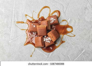 Delicious candies with caramel sauce and salt on light background, top view