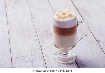 Delicious cappuccino on plank wooden table