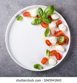 Delicious caprese salad with ripe cherry tomatoes and mini mozzarella cheese balls with fresh basil leaves. Italian healthy food concept with copy space. View from above.