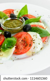 Delicious caprese salad with ripe tomatoes and mozzarella cheese with fresh basil leaves. Italian food.isolated white background