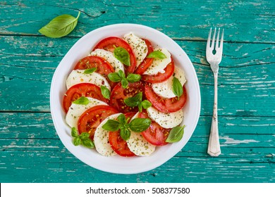 Delicious caprese salad with ripe tomatoes and mozzarella cheese with fresh basil leaves. Italian food.