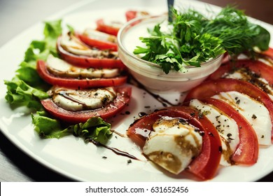 Delicious caprese salad with ripe tomatoes, mozzarella cheese and fresh basil leaves