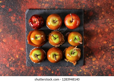 Delicious caramel apples with tree branches on slate plate