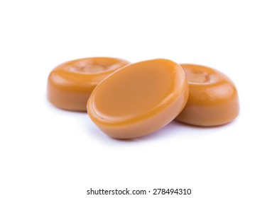 Delicious caramel candies on a white background.
