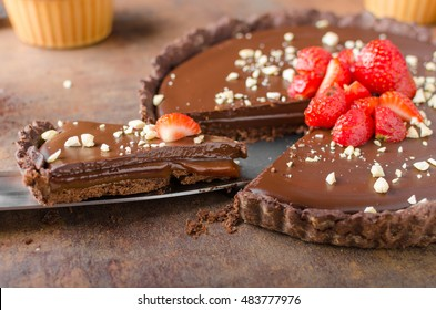 Delicious caramel chocolate tart, topped with nuts and strawberries